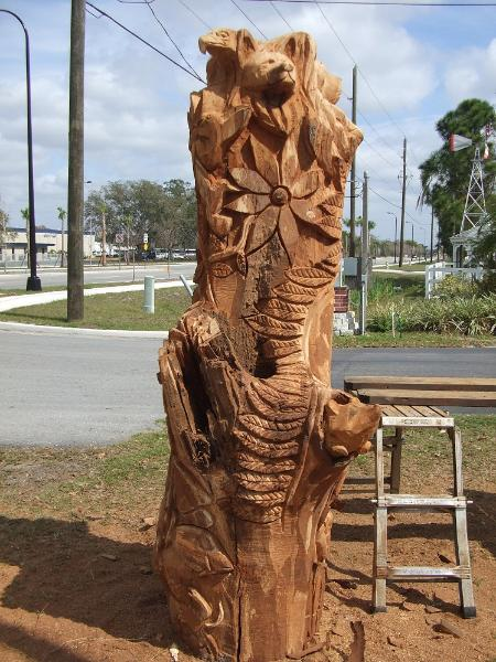 totem chainsaw sculpture with wolf , eagle and hummingbirds